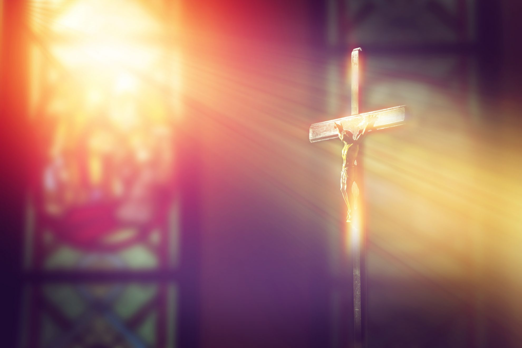 Crucifix with ray of light from stained glass